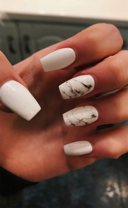 White manicure with black marbled ring and middle finger