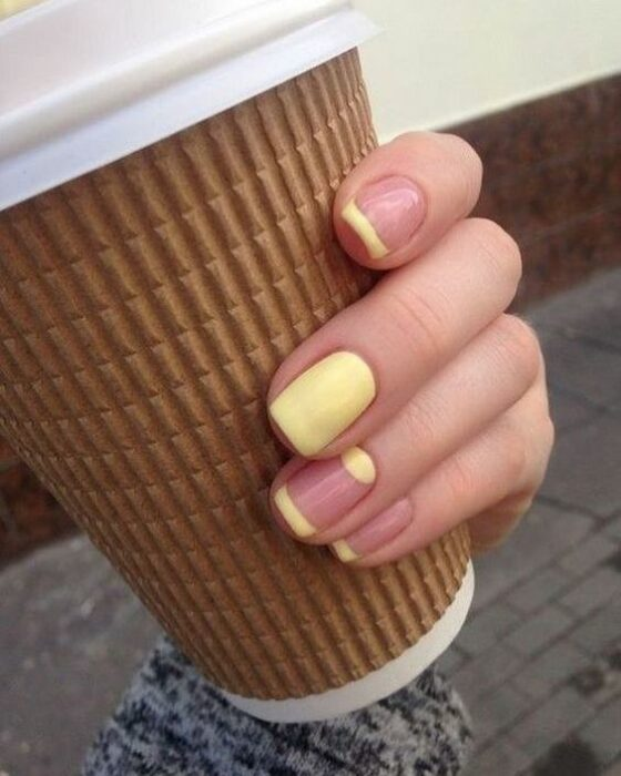 Manicure with bright yellow color and nude background