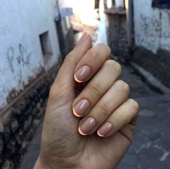 Manicure on nude background with French style in orange
