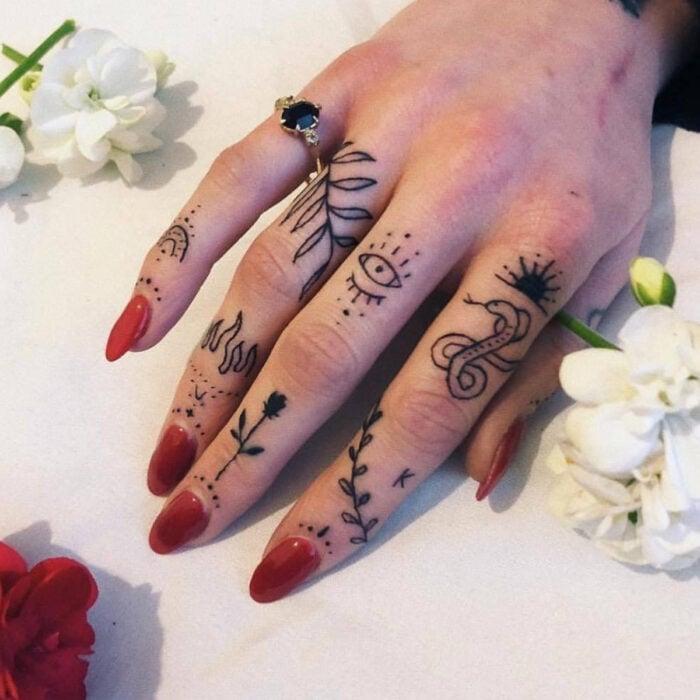 Manos bonitas de mujer con manicura, uñas largas en forma de almendra con esmalte color rojo, dedos con tatuajes de ojos, llamas, flores, serpiente, hojas y sol, anillo de piedra negra, flor blanca y roja