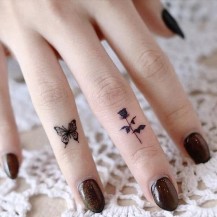 Pretty woman hands with manicure, short round nails with glitter brown polish, fingers with butterfly and rose tattoos