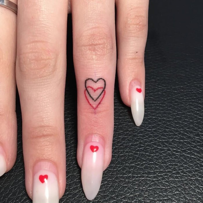 Pretty woman hands with manicure, long stiletto nails with white marble polish with heart design, finger with black and red hearts tattoo