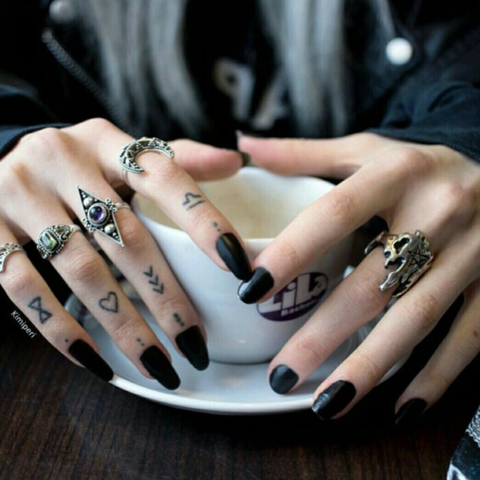 Pretty woman hands with manicure, long square nails, fingers with minimal tattoos of dots, arrows, hearts, hourglass, moon rings, skull, woman drinking coffee in a white cup