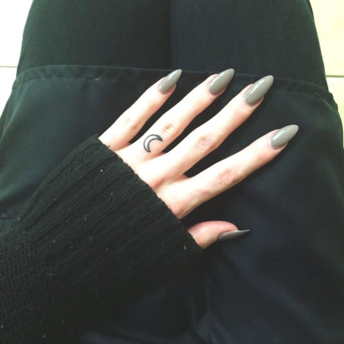 Pretty woman hands with manicure, long almond shaped nails with green gray polish, moon tattoo on middle finger