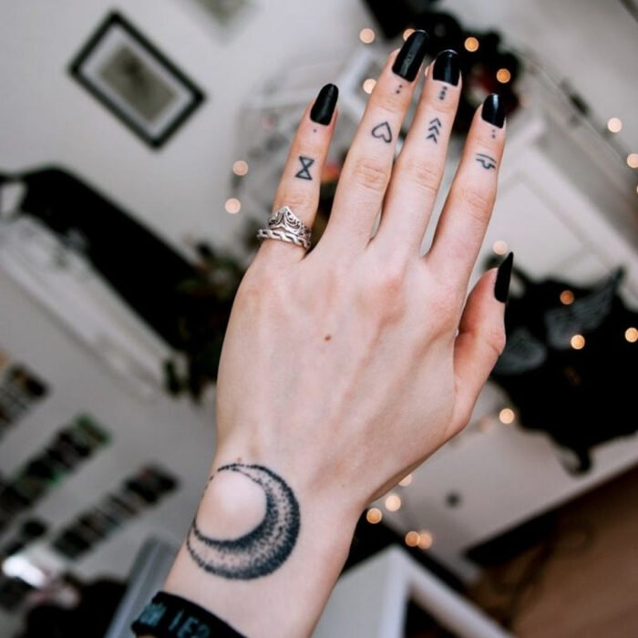 Pretty woman's hands with manicure, long square nails with black polish, fingers with hourglass, heart and arrow tattoos, moon tattoo with pointillism technique on the wrist, silver rings on the little finger