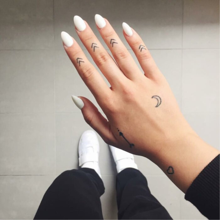 Pretty woman's hands with manicure, long almond-shaped nails with white polish, fingers with minimalist arrow tattoos, moon and heart tattoo on the hand and wrist, white tennis shoes