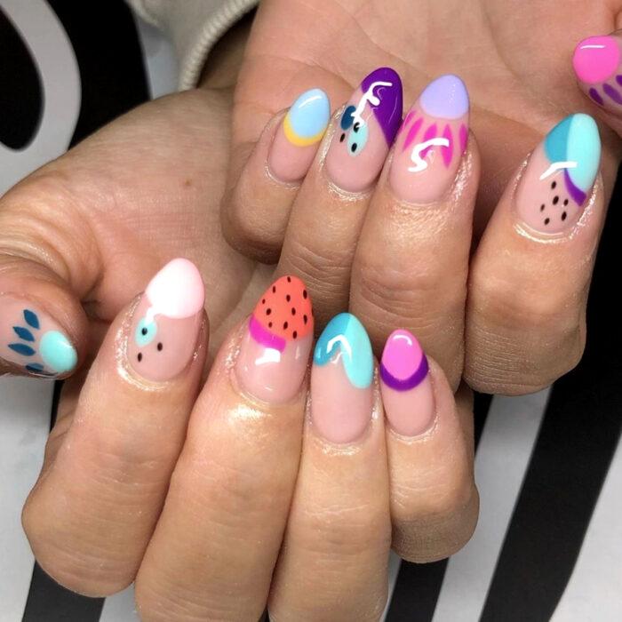 Diseños bonitos de manicura coloridos; uñas largas en forma de almendra pintadas con esmalte nude rosa y figuras azules, blancas, anaranjadas, rosas, moradas y puntitos negros
