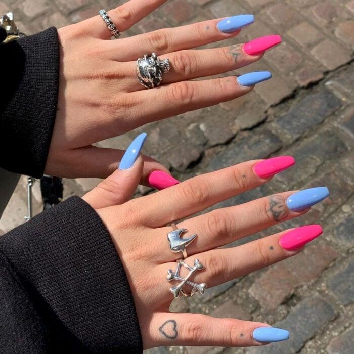 Diseños bonitos de manicura coloridos; manos d emujer con anillor rudos de calaveras, dientes y huesos, con tatuajes en los dedos de corazón, puntos y flores minimalistas, uñas largas cuadradas pintadas con esmaltes de colores azules y rosa