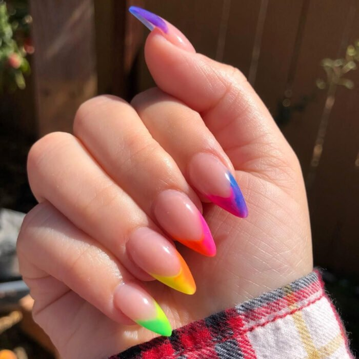 Pretty colorful manicure designs; women's hands with long stiletto nails painted with nude matte nail polish, and neon pink and green French style tips