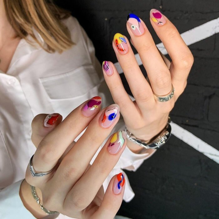 Pretty colorful manicure designs; woman hands with long almond shaped nails painted with polish of different shapes with abstract designs, blue, nude, pink, yellow, lilac, red, orange and mint green