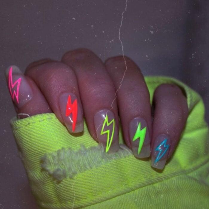 Diseños bonitos de manicura coloridos; manos de mujer con las uñas largas y cuadradas pintadas con diseños de rayos de colores rosa neón, anaranjado, verde y azul