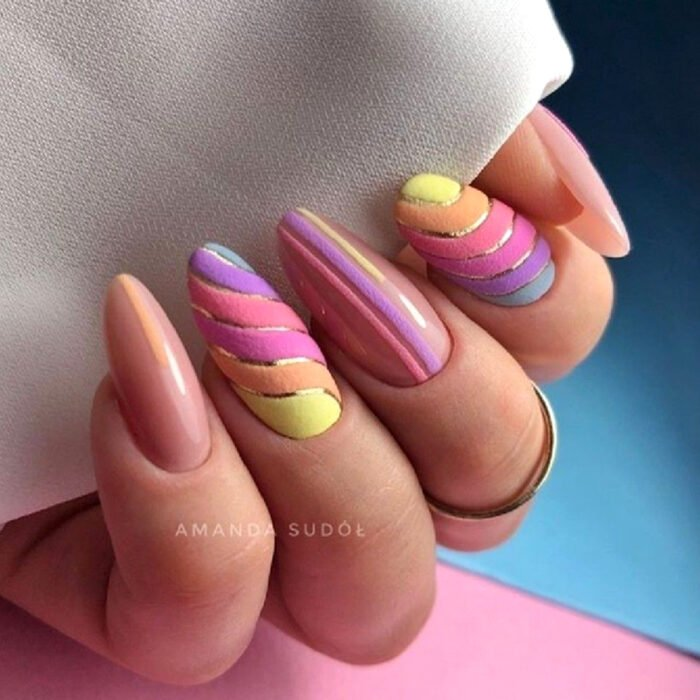 Pretty colorful manicure designs; woman's hands with long almond shaped nails painted with nude pink polish and textured plush, velvet, yellow, orange, pink, purple and blue