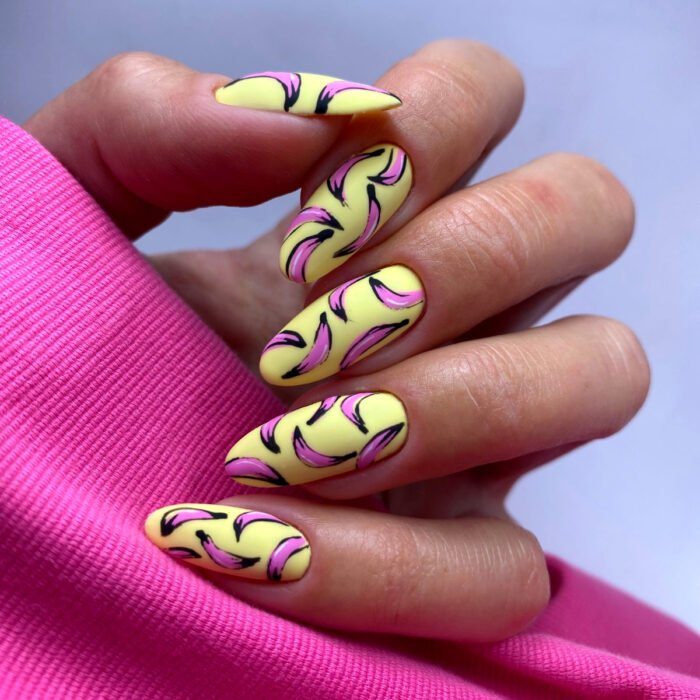 Pretty colorful manicure designs; woman's hand with long almond shaped nails painted with yellow and pink polish with banana pop art design