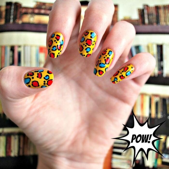 Diseños bonitos de manicura coloridos; manos de mujer con uñas largas redondas pintadas con esmalte de colores, base amarilla con diseño de animal print de leopardo rojo, negro y azul