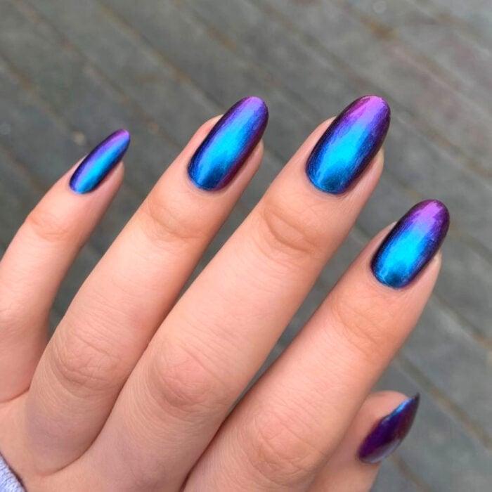 Diseños bonitos de manicura coloridos; mano de mujer con uñas largas en forma de almendra, pintadas con esmalte holográfico de colores morado y azul