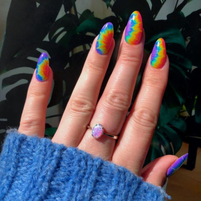 Diseños bonitos de manicura coloridos; uñas largas en forma de almendra pintadas con esmaltes de colores jipis del arcoíris, morado, azul fuerte y claro, verde, amarillo, anaranjado y rojo, anillo de piedra rosa