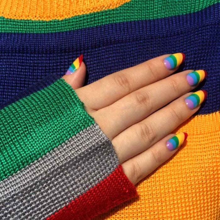 Diseños bonitos de manicura coloridos; uñas largas en forma de almendra pintadas con esmalte de colores del arcoíris, morado, azul, verde, amarillo, anaranjado y rojo