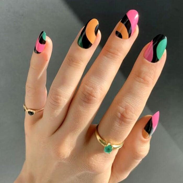 Diseños bonitos de manicura coloridos; uñas largas redondas pintadas con esmaltes de colores negro, rosa, verde y anaranjado, anillos sencillos de piedras