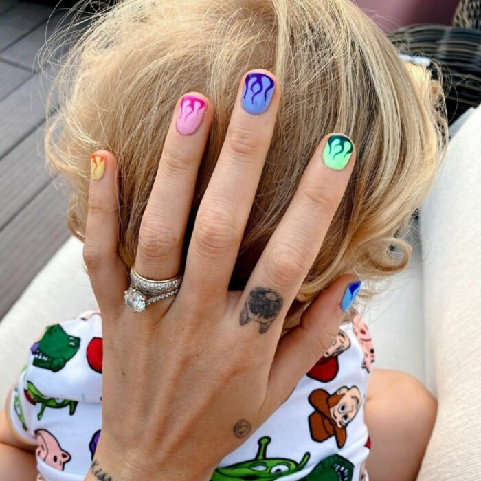 Pretty colorful manicure designs; woman's hand with short, round nails painted with yellow, orange, pink, purple, green and blue nail polish, with flame designs