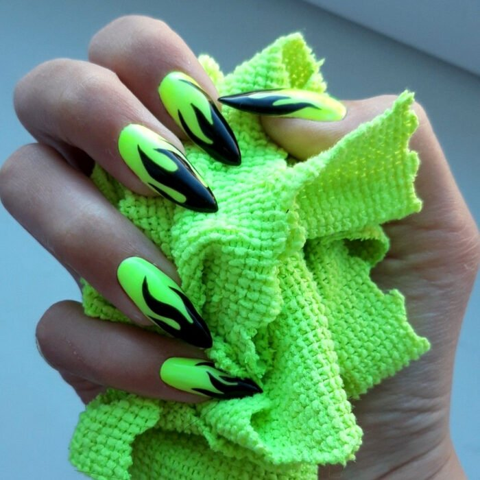 Diseños bonitos de manicura coloridos; manos de mujer con uñas largas stiletto pintadas con esmalte negro y verde neón