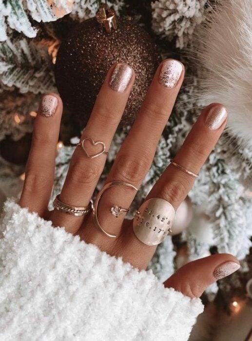 Chica con manicura en color rosa con glitter; Uñas con glitter para Navidad