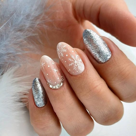 Silver nails with white decorations in the shape of snowflakes; Glitter nails for Christmas