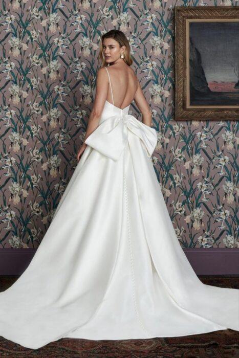 Chica usando un vestido de color blanco con un detalle de moño en la parte trasera