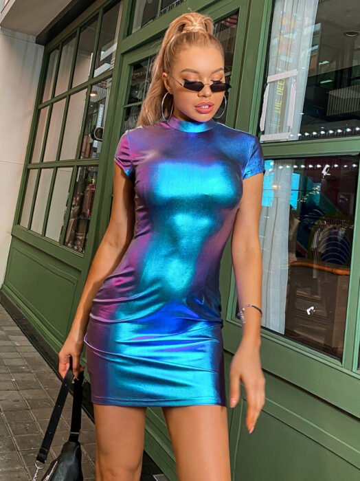 Iridescent, holographic dress with neckline, sleeves, short, blonde woman with long, straight blonde hair combed into a ponytail, wearing small sunglasses