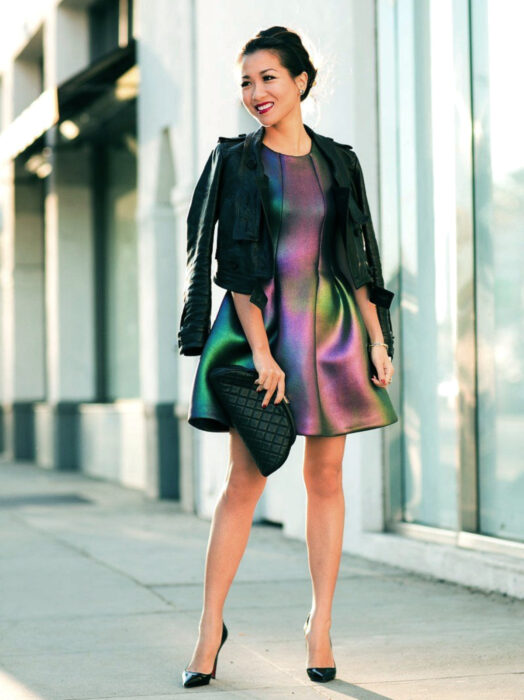 Iridescent, holographic above knee dress, woman on the street in black sneakers, black denim jacket, clutch bag, probing, with party hairstyle