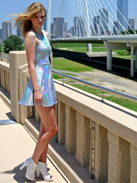 Iridescent dress, holographic white sleeveless, short, blonde woman with tousled medium hair
