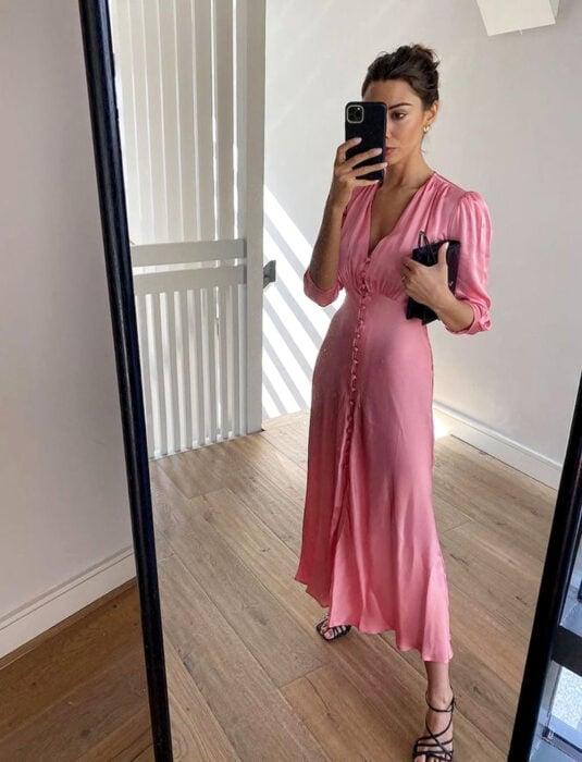 Mujer tomándose una selfie con su celular frente al espejo, vestido rosa largo y liso, de mangas a los codos, escote en v y botones al frente, peonado de chongo recogido y cabello castaño, bolsa de mano negra, sandalias de tacón negras