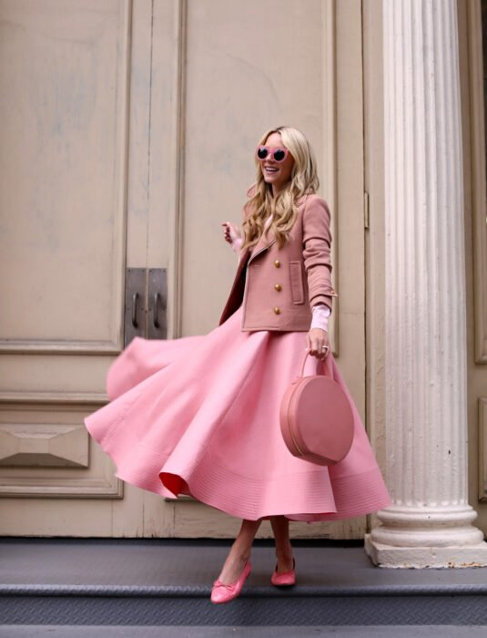 Woman smiling on the street in front of a large door, long, wavy and flowing blonde hair, Barbie sunglasses, long pink flared dress, dress jacket, flats, round handbag