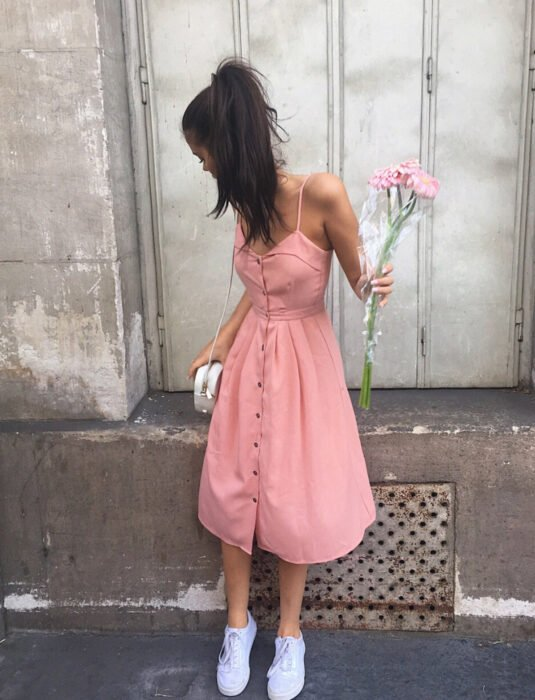 Brunette woman in a pink dress with straps, buttons and below the knees, with a bouquet of flowers, ivory bag, white tennis shoes, brown hair, long, straight combed with a high ponytail