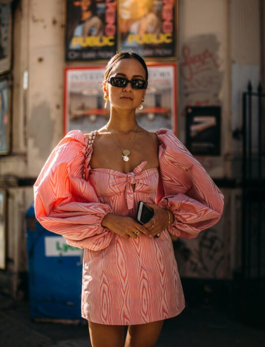 Woman in the street, dark brown hair, combed with a low tail, rectangular dark sunglasses, golden earrings and necklaces, pink and white dress, puffed sleeves, square neckline, with cell phone in hand