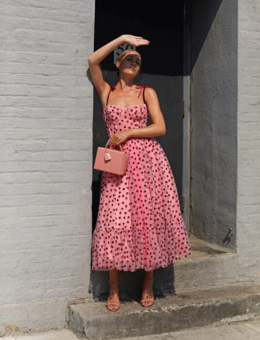 Woman in the street covering her face from the sun, wearing a pink strapless dress, with a heart print, corset, tulle fabric, ankle length, nude high-heeled sandals, rectangular handbag