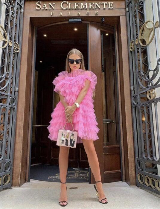 Girl in front of wooden door, long straight blond brown hair, with heart-shaped dark sunglasses, pink dress of hollans, rectangular handbag, black gold-heeled sandals, woman's watch