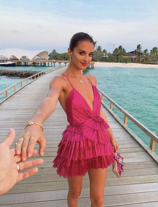 Brunette woman on the beach, in port on the sea, dark brown hair, combed in a low bun, pink Mexican beach dress with flounces, suspenders, v-neckline, sandals in her hands