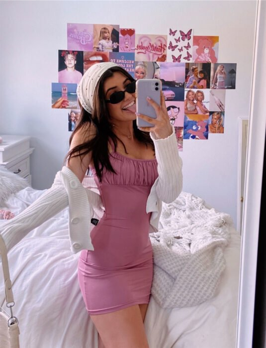 Woman taking a selfie in front of the mirror with her cell phone, pink mini dress with suspenders, tight to the body, bandage in her brown hair, straight and loose, white knitted sweater, black oval sunglasses, wall full of posters of artists and films