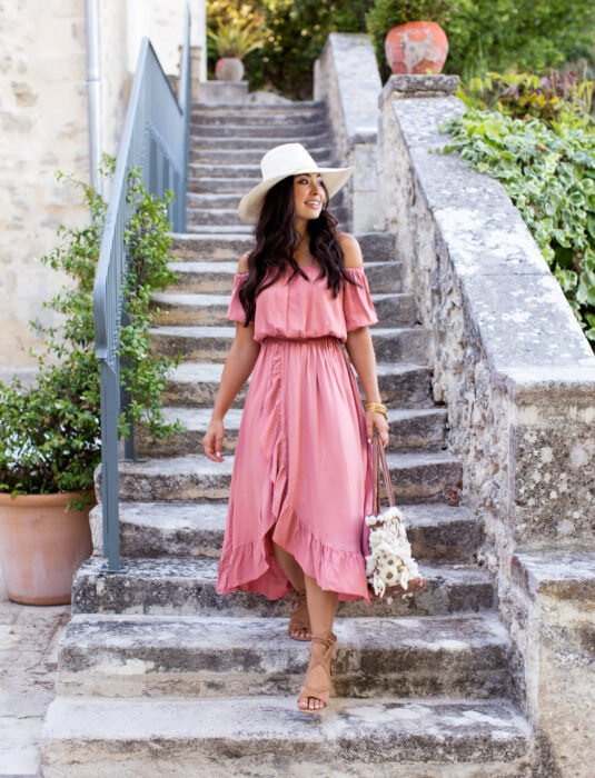 Woman going down stone stairs with plants around, dark brown hair, wavy, long and loose, with pink beach dress without shoulders and even shawls, brown flat sandals, handbag, white hat