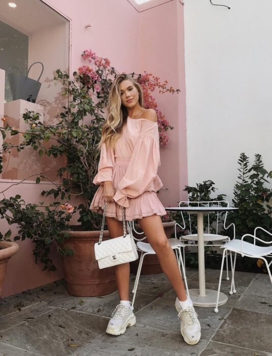 Girl with blonde hair, long, wavy and loose, with pink minidress, baggy, with shoulders, with sleeves, white skechers tennis shoes, handbag with chain, bougainvillea plant