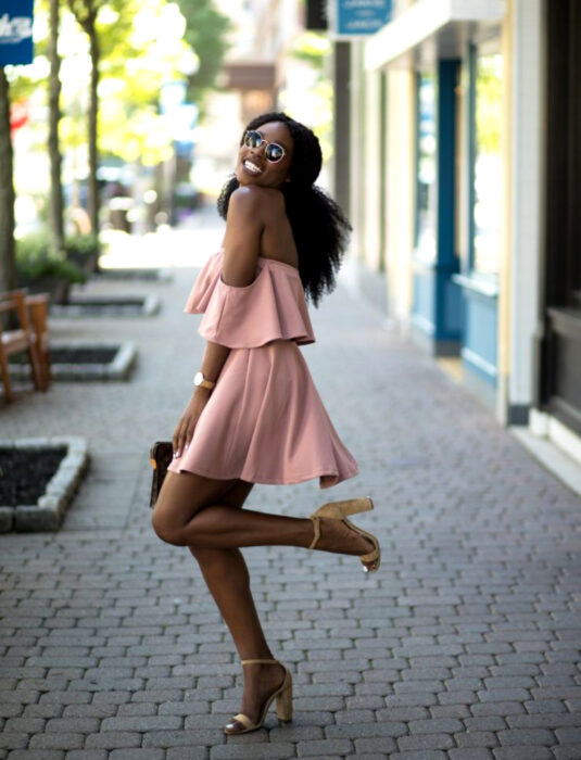 Brunette girl smiling on the street, Chinese hair, black, afro, fluffy hairstyle with half ponytail, dark sunglasses, pink shoulderless minidress, camel-colored heels, women's watch