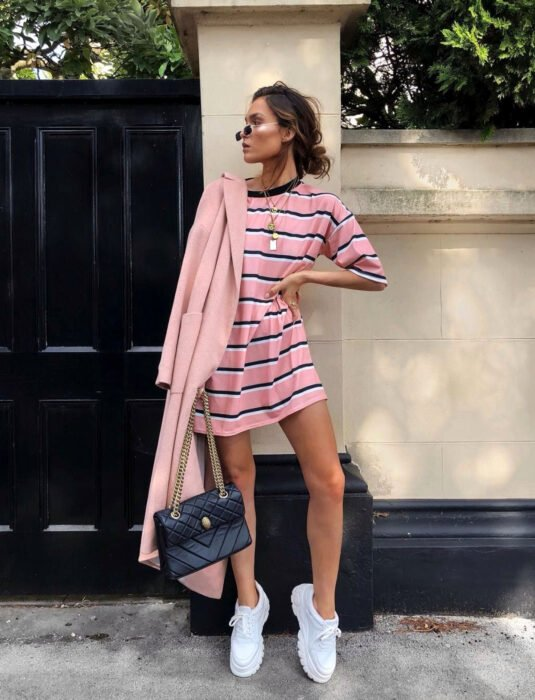 Woman leaning against the wall posing with her hand on her waist for the photo, brown hair with a disheveled bun hairstyle, shirt as a dress, pink with horizontal black stripes, suede blazer, white skechers tennis shoes, black bag with gold chains