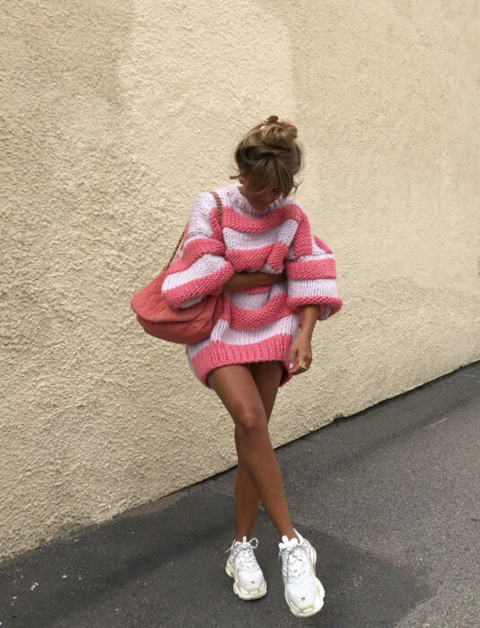 Dark-haired woman in the street, with blond hair with a high bun hairstyle, in an oversized sweater knitted with horizontal white and pink stripes, large sleeves, pink suede bag, white skechers tennis shoes