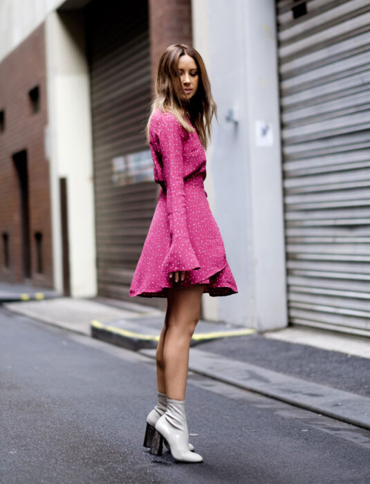Woman on the street, straight, medium brown blond hair, loose with a part in the middle, Mexican pink dress with white dots, flared sleeves, gray high-heeled 70s boots