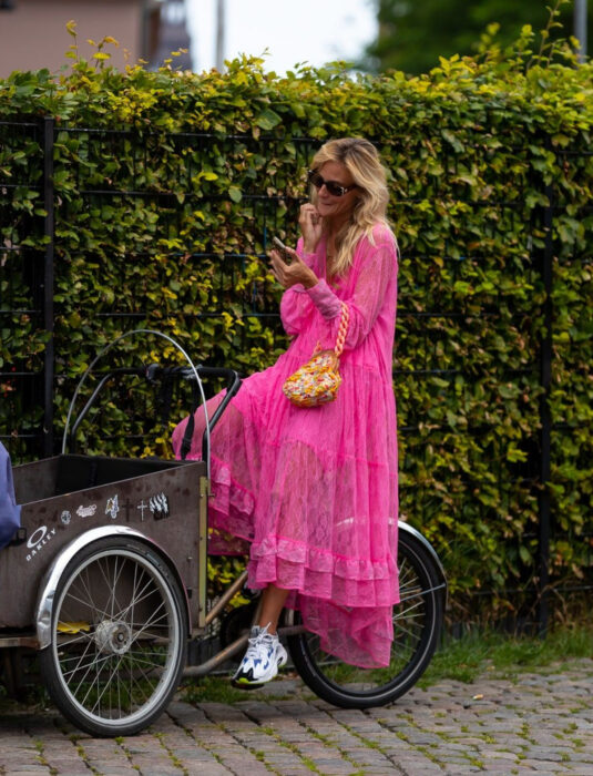Woman on tricycle in front of a bush in the street, looking at her cell phone, blonde hair, wavy, loose, disheveled, medium, with neon pink lace dress and ankle-length flounces, white skechers tennis shoes with blue, black and berdes details, bag yellow handheld with chunky chain, rectangular sunglasses