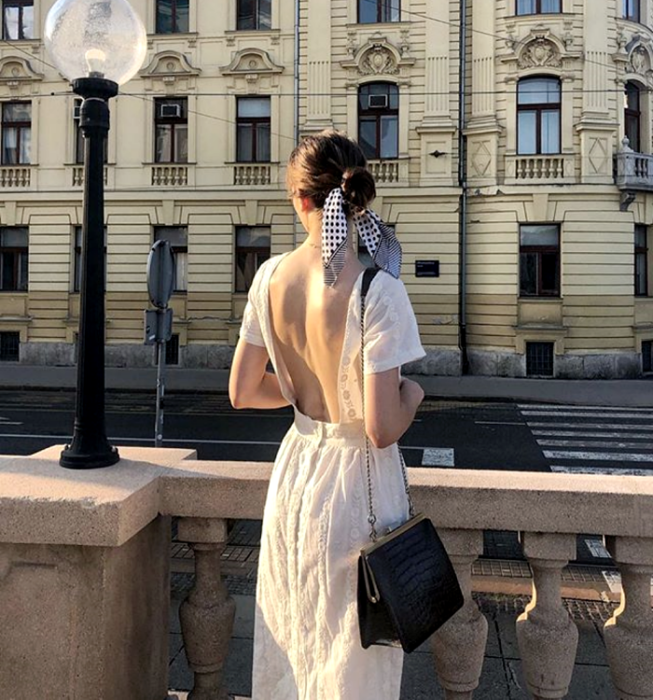 dark haired girl wearing short sleeve white dress with neckline at back, black handbag with chain strap