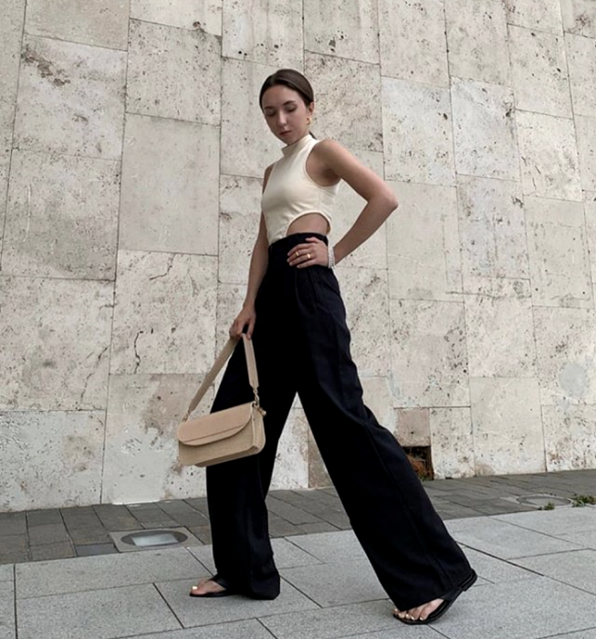 brown haired girl wearing white sleeveless top with high neck and low waist, flared black dress pants and beige handbag