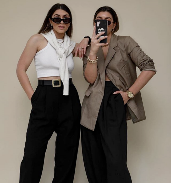 two brown haired girls wearing sunglasses, white tank top with high neck, oversized brown blazer, black dress pants and white sweater
