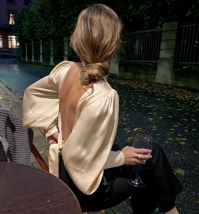 blonde girl wearing a champagne satin blouse with puff sleeves with neckline at the back, black dress pants
