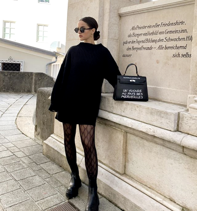 black haired girl with sunglasses, black oversized sweater, black mini skirt, black fishnet stockings and black platform boots, black clutch bag with white letters